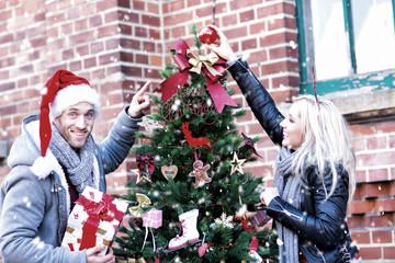 Pärchen schmückt zusammen den Weihnachtsbaum