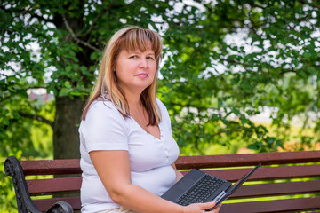 beautiful mature woman on a park bench with a laptop