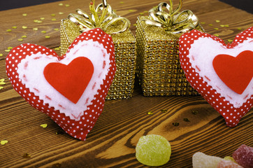 Red hearts, two golden gift and fruit candy.
