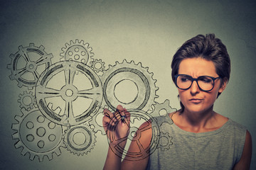 Gears and ideas creativity concept. Woman in glasses drawing gears with pen