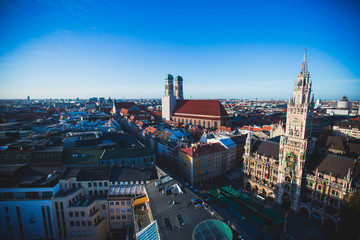 Beautiful super wide-angle sunny aerial view of Munich, Bayern, Bavaria, Germany with skyline and scenery beyond the city, seen from the observation deck of St. Peter Church