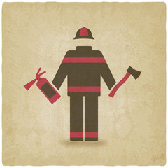 Fireman with extinguisher and axe old background