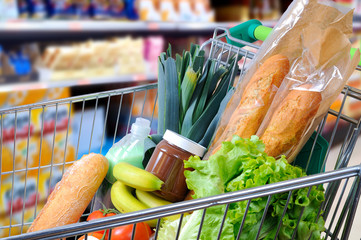 Shopping cart full of food in the supermarket side view