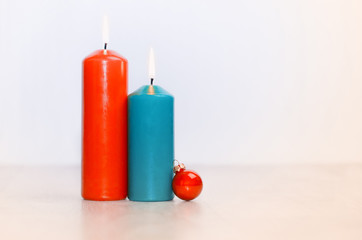 Two candles and a Christmas ball on a wooden surface