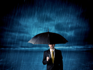 Business man standing in rain with an umbrella