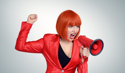 Business redhead woman in red screaming into a megaphone