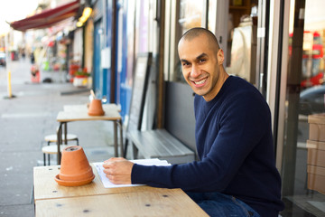 Young man sitting outside a coffee shop