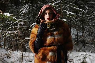 beautiful young Woman in fashionable Fur and scarf at night in winter forest