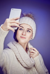 Woman in sweater and winter hat taking selfie.