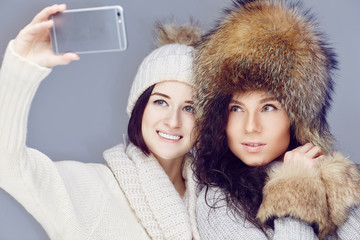 Two girlfriends taking picture on smartphone.
