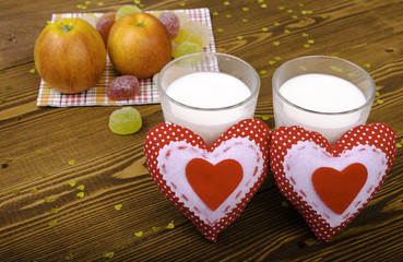 Two hearts, apples on a napkin and two glasses of milk.