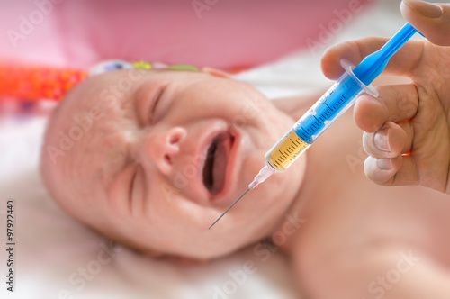 Vaccination concept - syringe and crying baby