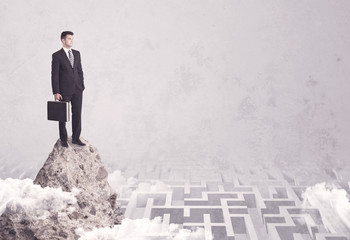 Businessman on cliff above labyrinth