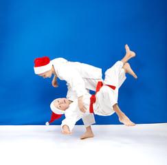 Children in judogi are training throws