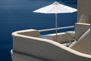 White umbrella on balcony resort house and Aegean sea, Santorini