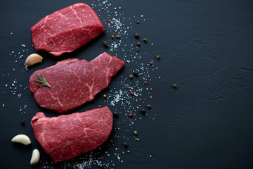 Deurstickers Vlees Raw fresh marbled beef steaks on a black wooden surface
