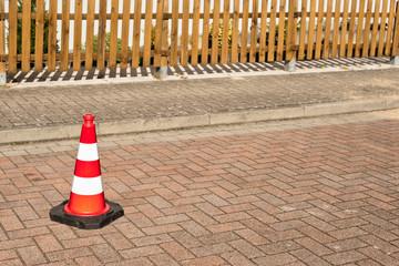 Eine Pilone steht auf einer Strasse aus Beton-Pflastersteinen