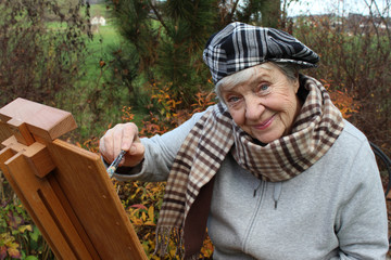 happy senior woman painting picture on nature