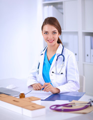Beautiful young smiling female doctor sitting at the desk and writing