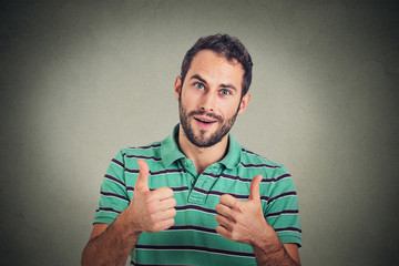 Happy man giving thumbs up sign. Positive human face expression body language .