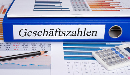 Geschäftszahlen Ordner mit Statistik und Taschenrechner im Büro