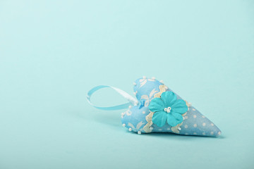 One textile heart with flower on blue background