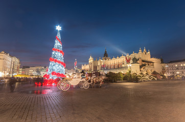 Krakow, Poland, Main Market square and Cloth Hall in the winter season, during Christmas fairs decorated with Christmas tree.