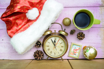 Alarm clock with Christmas ornaments beside Santa hat and coffee