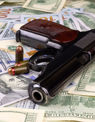 A pistol with bullets on the banknotes of American dollars, crime or corruption concept.
