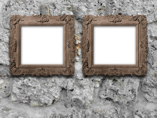 Two brown baroque frames on grey stone wall background