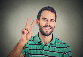 headshot young man, handsome student holding up peace victory, two sign