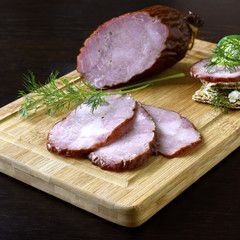Traditional smoked sausage with dill, sandwich and vegetables on a wooden cutting board