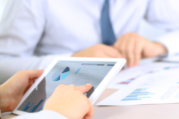 Business colleagues working and analyzing financial graphs on a