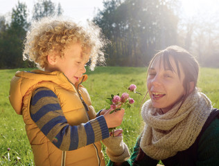 Little boy in autumn clothes gives his mom a flower, close-up