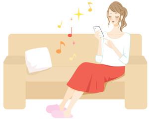 スマートフォンで音楽鑑賞をする女性 室内