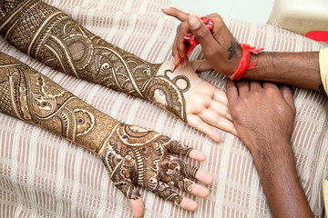 Henna being applied to bride's hand