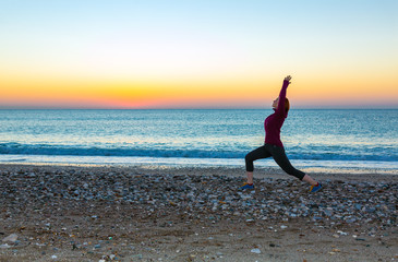 Young Woman doing yoga Exercise on tropical Beach at Sunrise