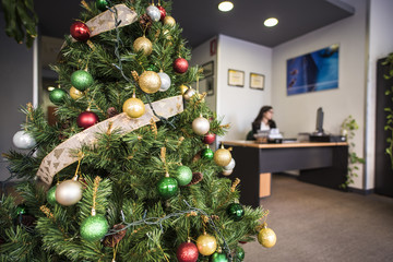 Decorated Christmas tree in office. Woman on background