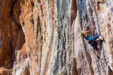 Blond Female Climber ascending Vertical Orange Rock
