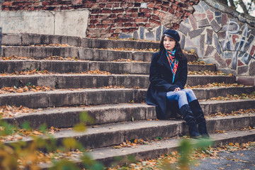 Woman sitting on old stairs in autumn park