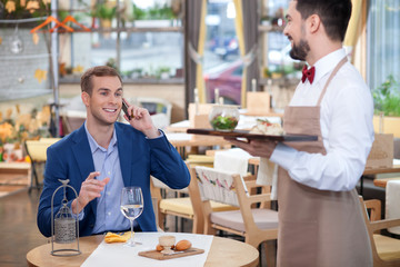 Attractive male cafe worker is serving the customer