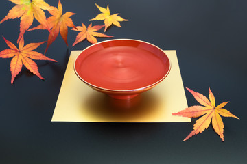 vermilion lacquer coated sake cup and maple leaves. vermilion sake cups are used for festive meals, especially for New Year celebration or wedding ceremonies.