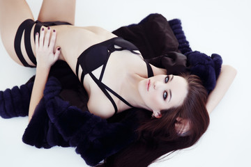 Beautiful woman in the black lingerie and a fur coat is posing on the floor
