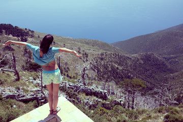 Young woman overlooking sea horizon.Carefree tourist stands on mountain peak with arms outstretched in freedom pose.Beautiful view,enjoying summer vacation.High mountain peak with beautiful sea view