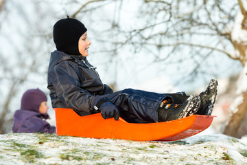 Boy sitting in sledge on sunny winter day