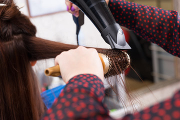 Stylist Drying Hair of Brunette Client in Salon