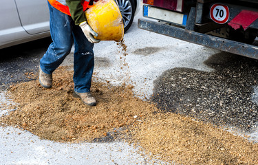 worker committed to the repair of a large pit road with inert mixed stabilized. With motion blure