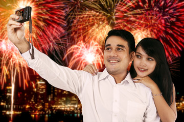 Couple taking selfie photo with the fireworks background