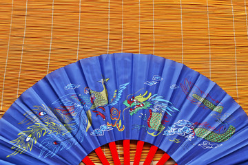 Blue  Chinese  with dragon fan on bamboo background