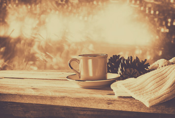 selective focus and abstract photo of cozy knitted scarf with to cup of coffee on a wooden table. faded style retro filtered and toned.